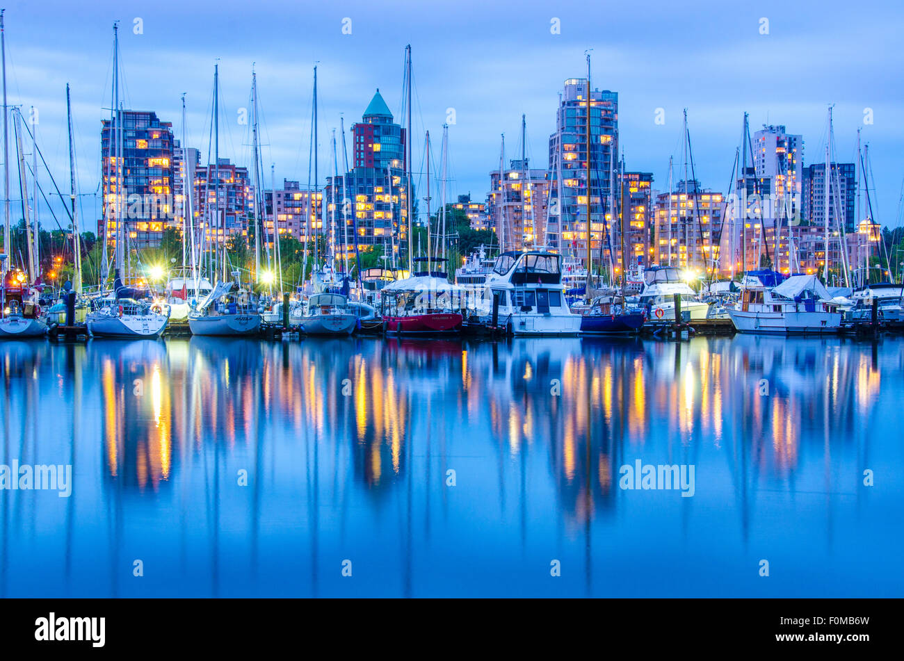 Water reflections in Vancouver of harbour buildings and boats. - Stock Image