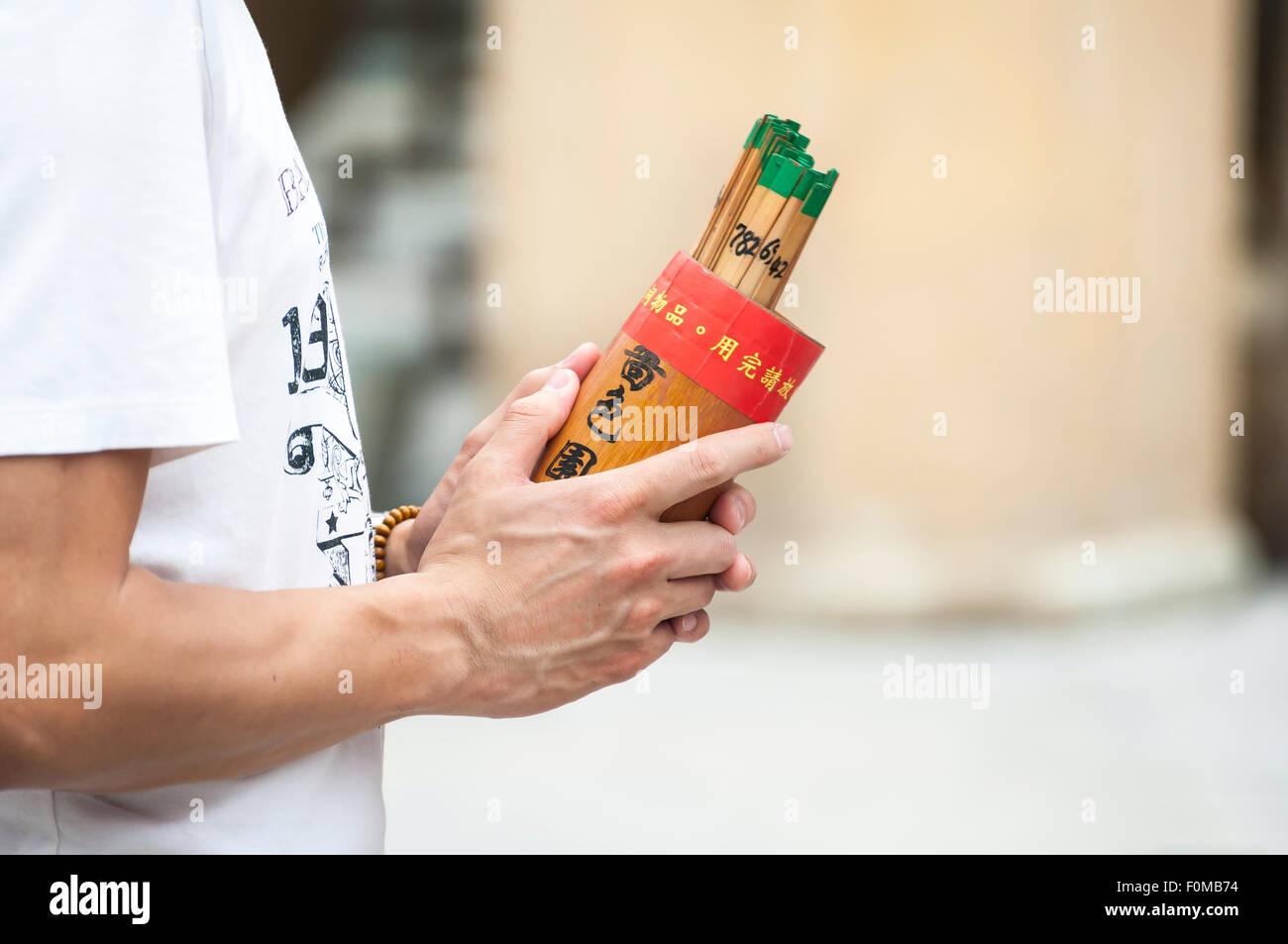 Man holds a box of fortune sticks at Wong Tai Sin temple, Hong Kong - Stock Image