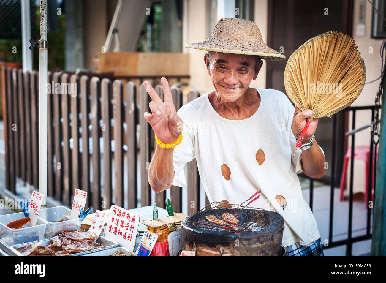 Hawker selling grilled squid at Tai O village, Lantau Island, Hong Kong - Stock Image
