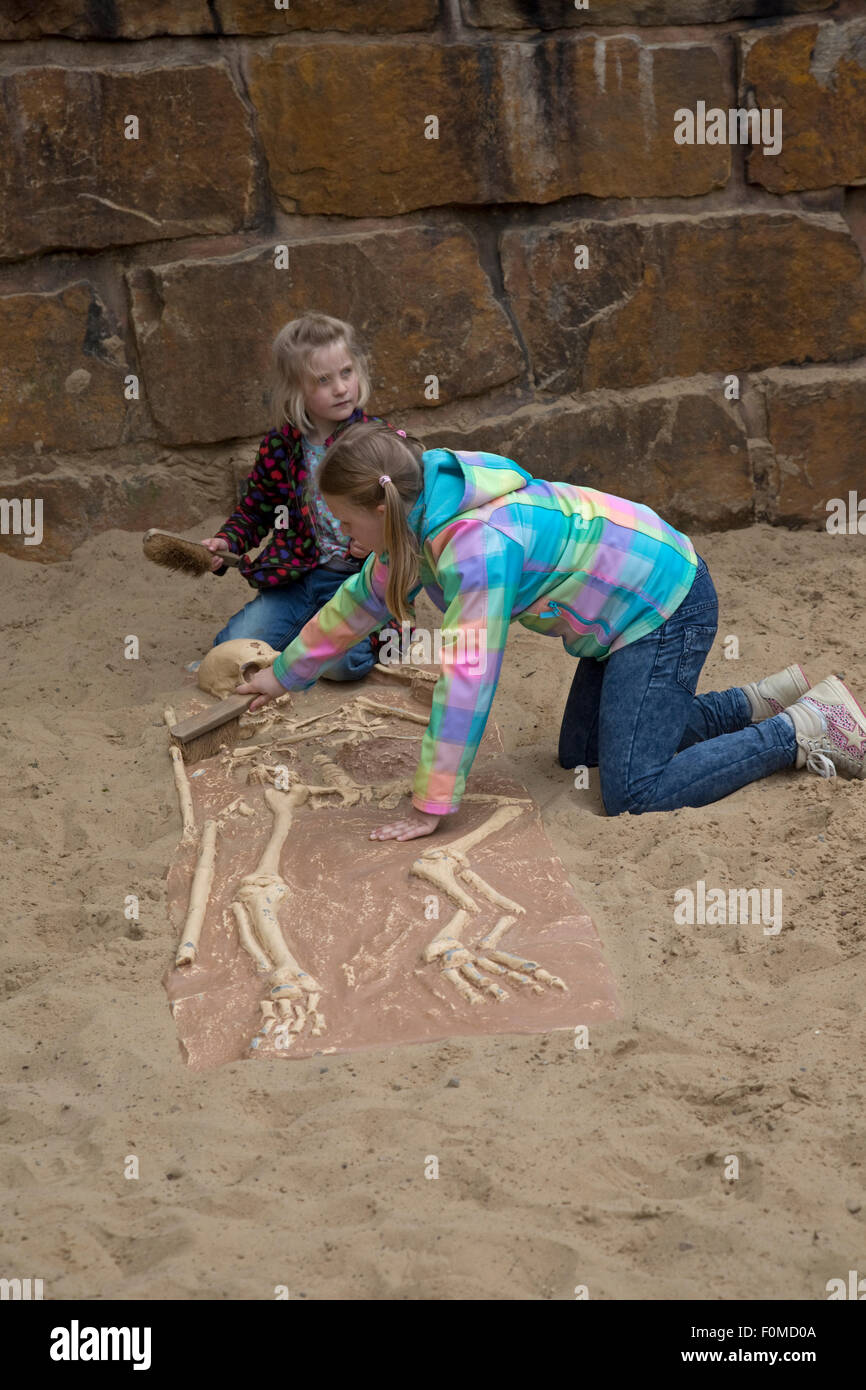 Two young girls archeologists excavating skeleton Dinosaurier Park Germany - Stock Image