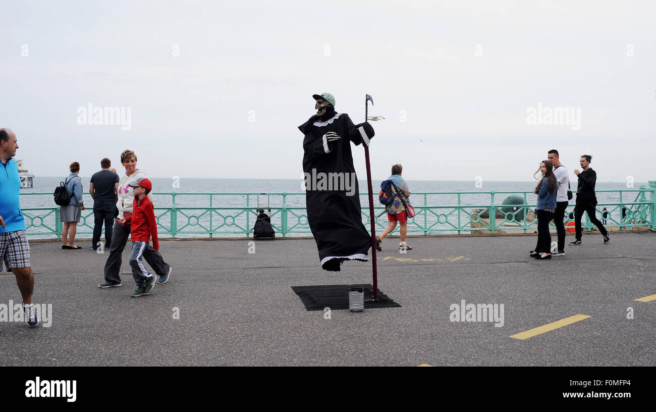 Brighton, UK. 18th August, 2015. A street performer dressed as the Grim Reaper stands in mid air during dull weather - Stock Image