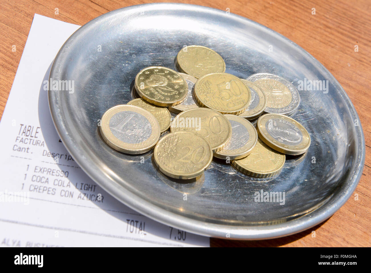Drinks bill and Euro coins as payment on a silver tray after being given the bill in a cafe in Marbella Stock Photo
