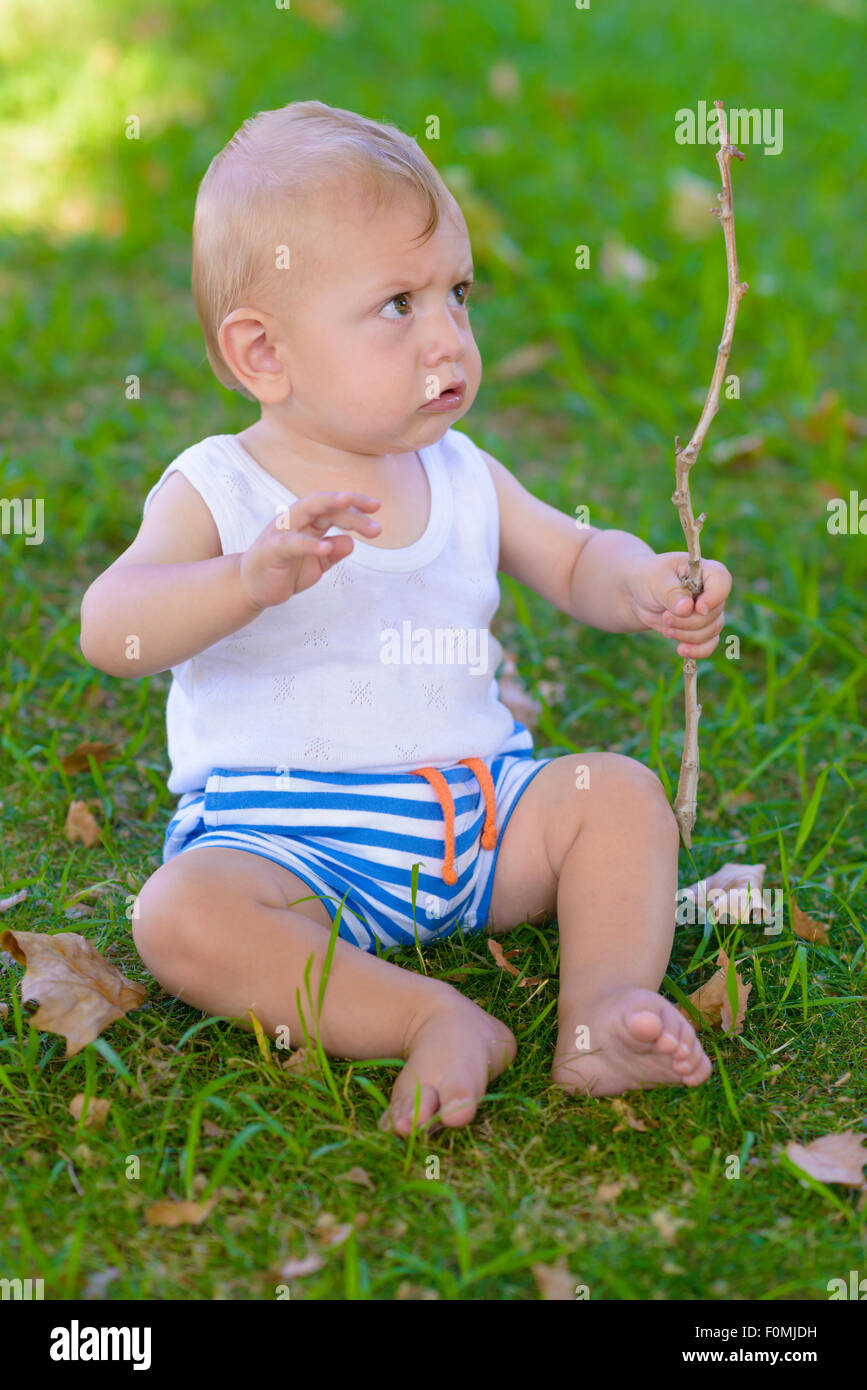 Serious Baby Boy playing with a twig with furrowed look - Stock Image