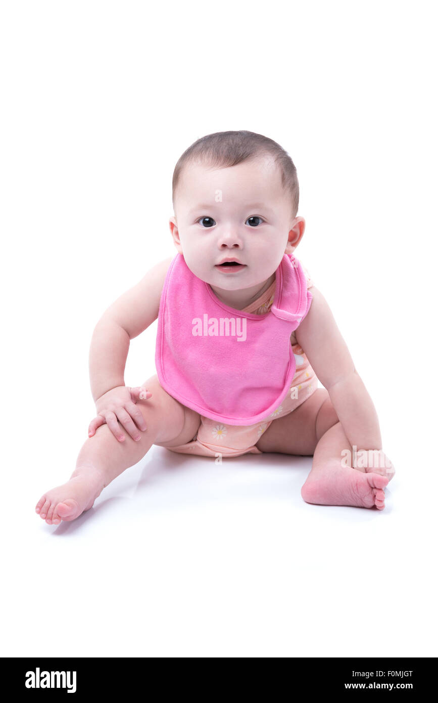 A cute 1 year old girl wearing a pink bib sitting on white. - Stock Image