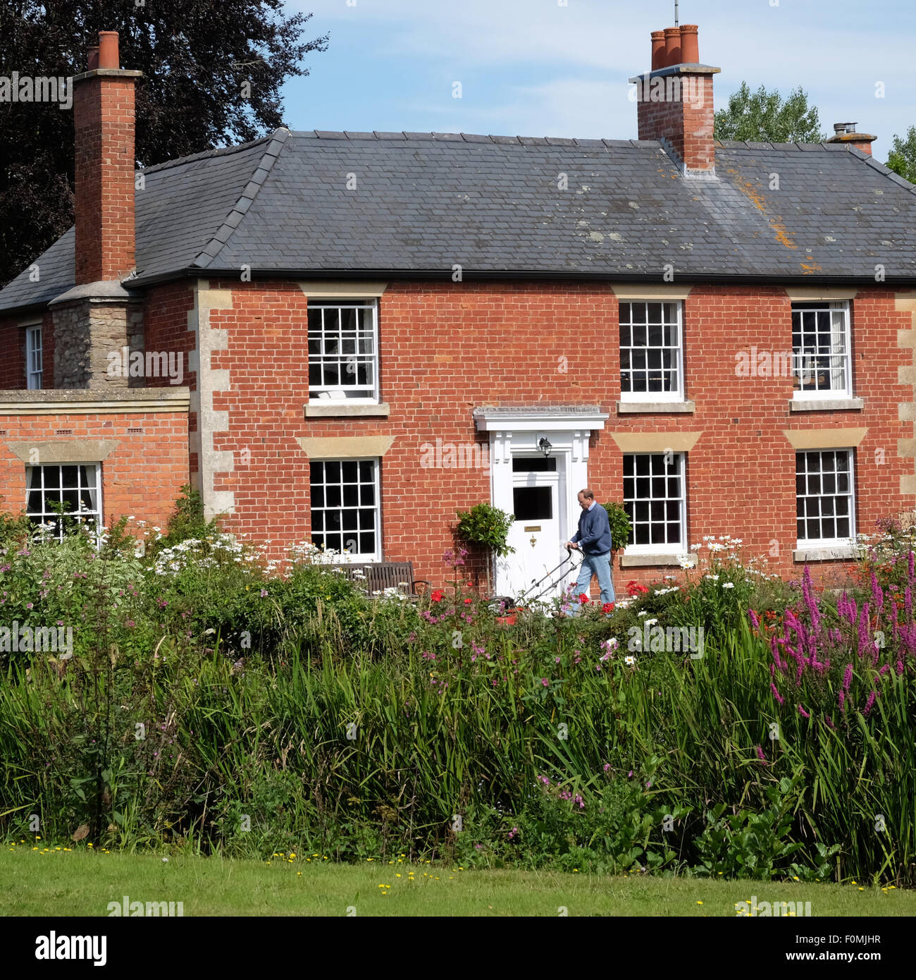 Eardisland Herefordshire man cutting lawn grass in elegant old red brick property UK - Stock Image