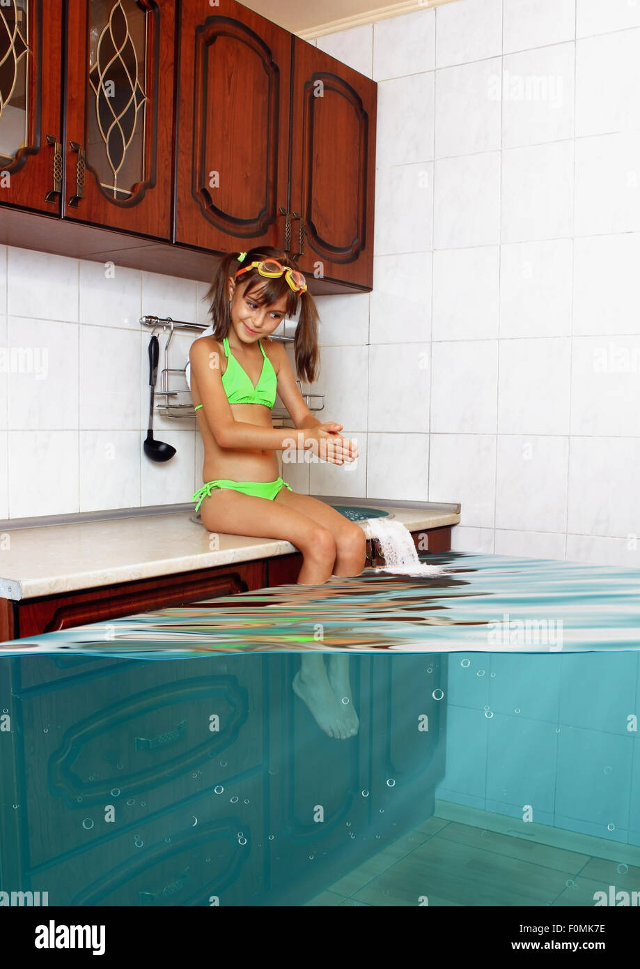 Child girl make mess, flooded kitchen imitating swimming pool, funny concept - Stock Image