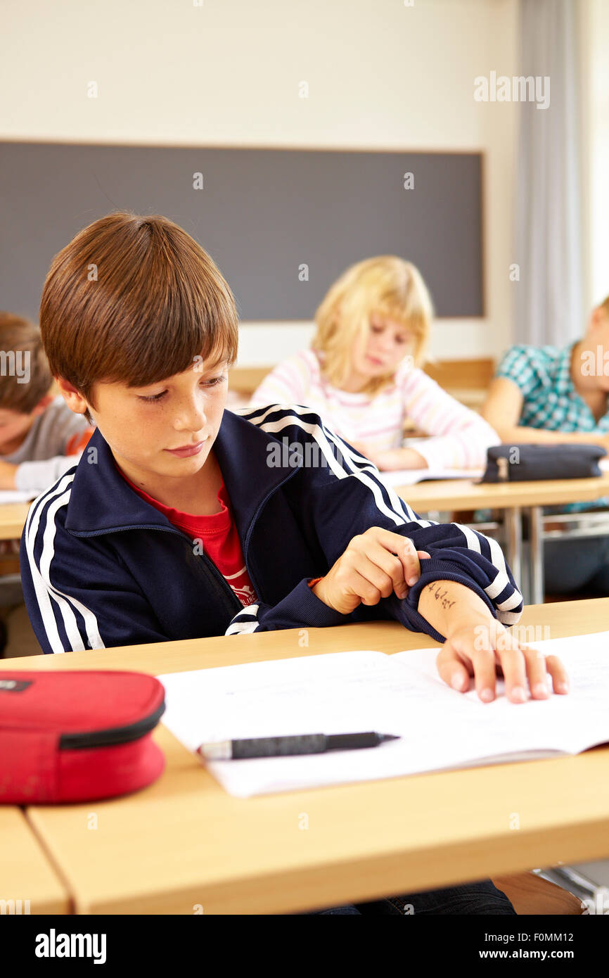 Schoolboy while cheating at school - Stock Image