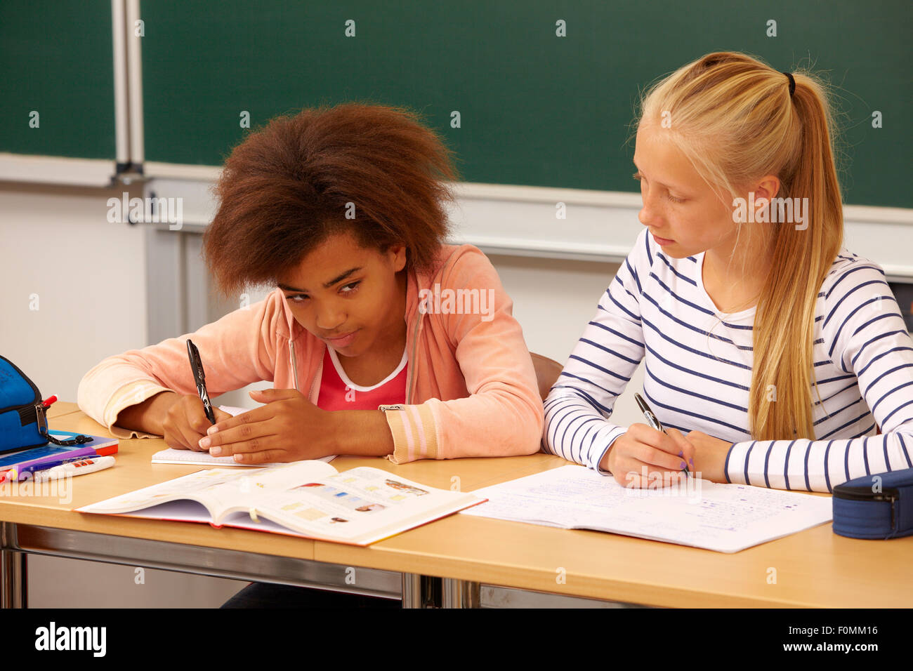 Girl allows her classmate not to copy - Stock Image
