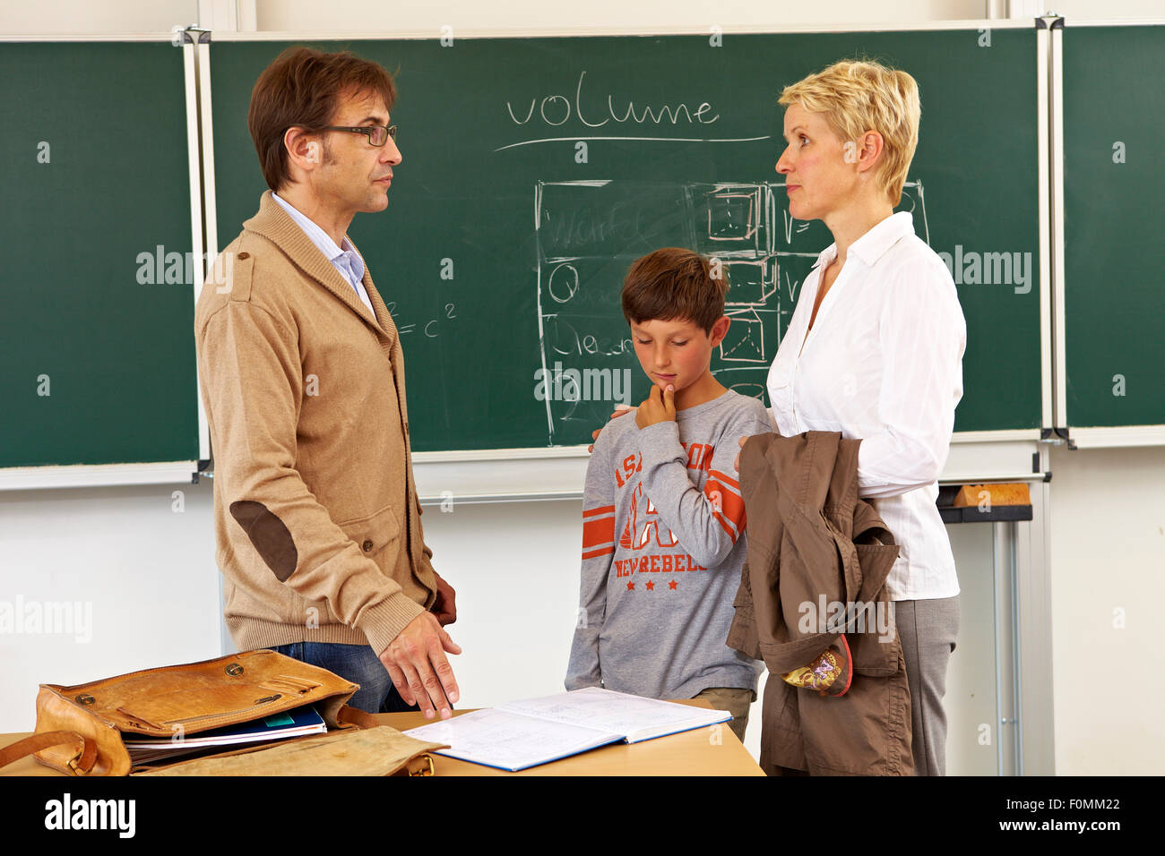 Mother and son talking with the teacher - Stock Image