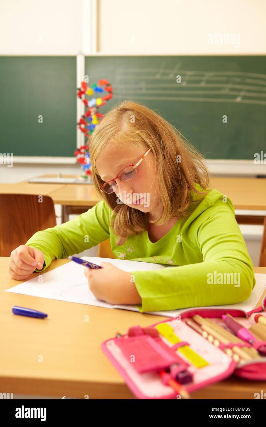 Schoolgirl writes with the left hand - Stock Image