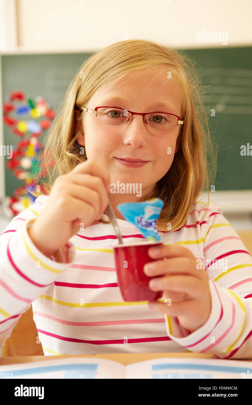 School child eats a sweet fruit preparation - Stock Image