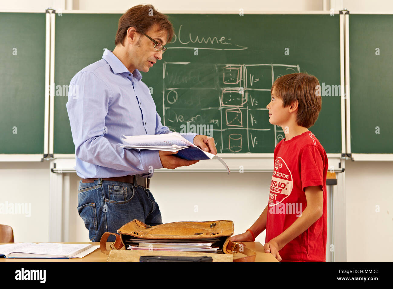 Teacher with pupil in front of blackboard - Stock Image