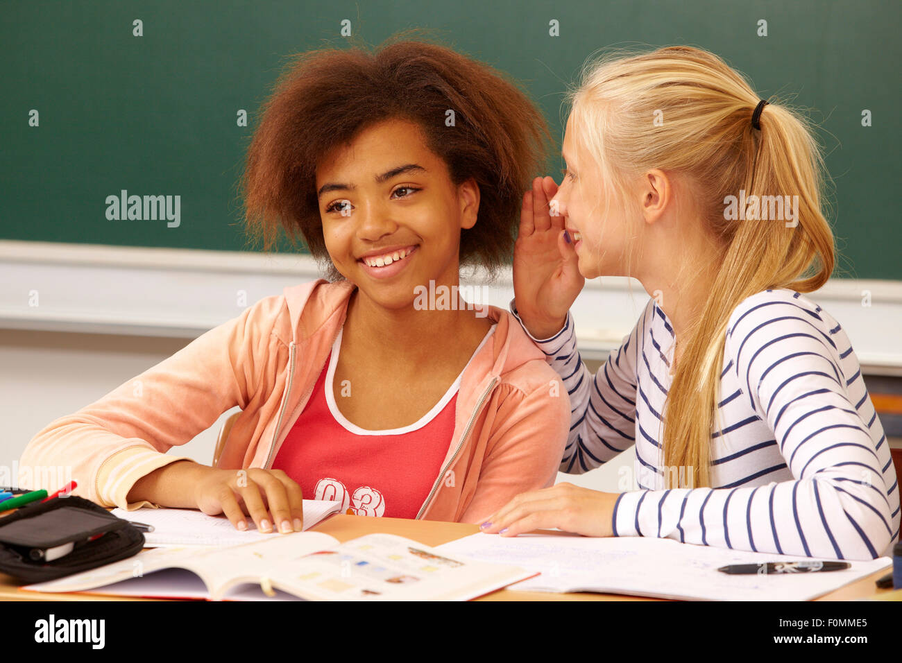 Two girls at school while whispering - Stock Image