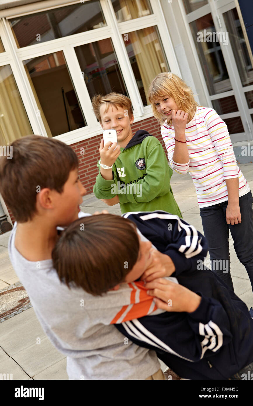 Cyber bullying in the schoolyard - Stock Image