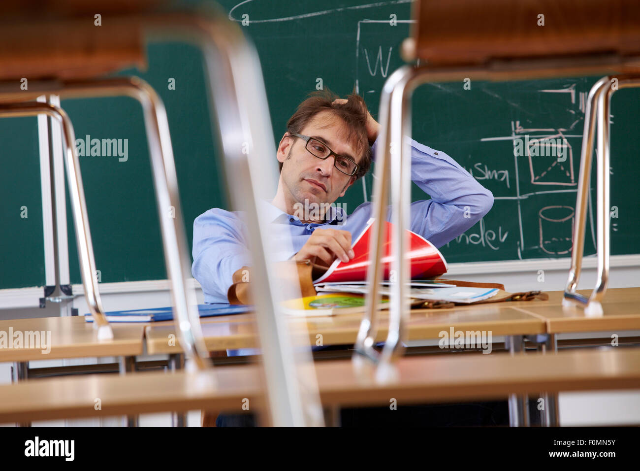 Exhausted teacher in the classroom - Stock Image