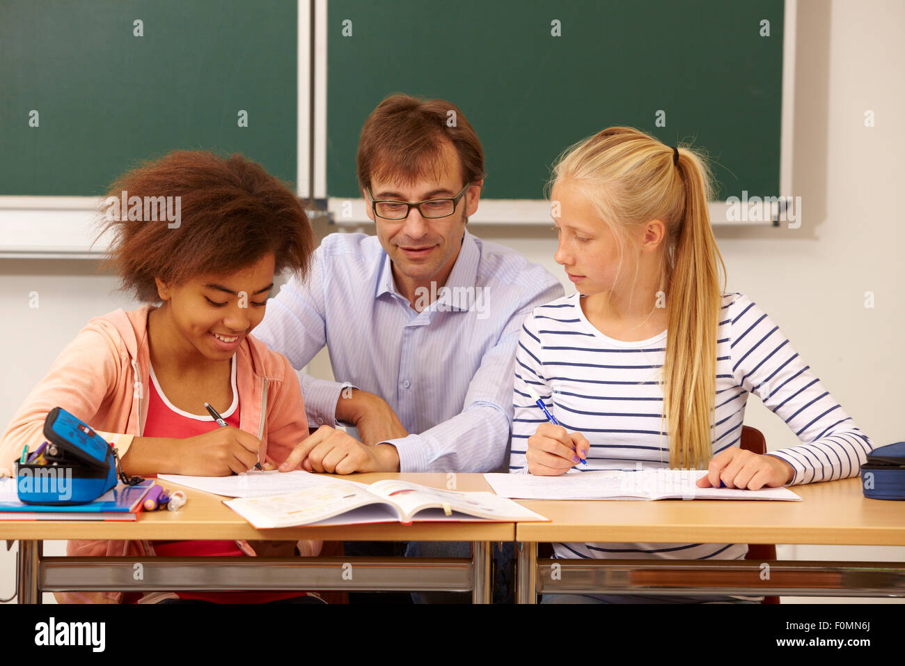 Teacher helps two schoolgirls in the lessons - Stock Image