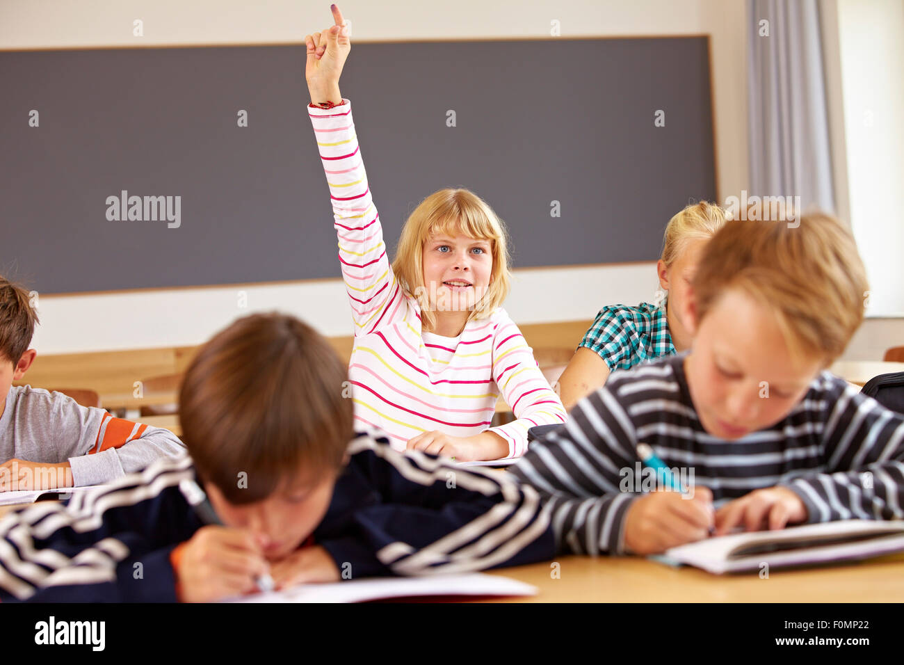 Girl logs on in the classroom - Stock Image