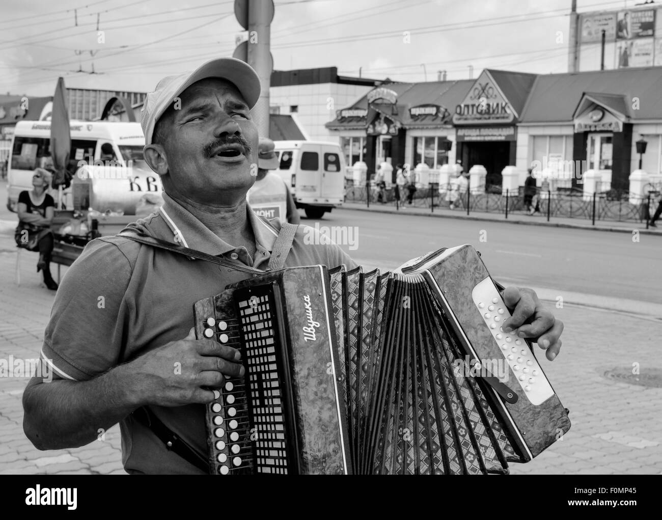 Faced with his disability this blind accordian player plays music for shoppers in Sterlitamak Russia in the hope - Stock Image