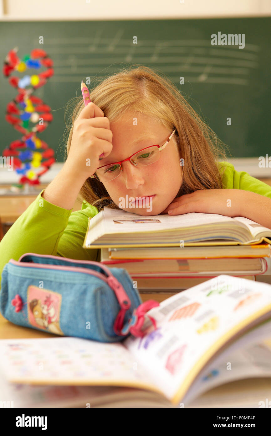 Exhausted schoolchild with a stack of books - Stock Image