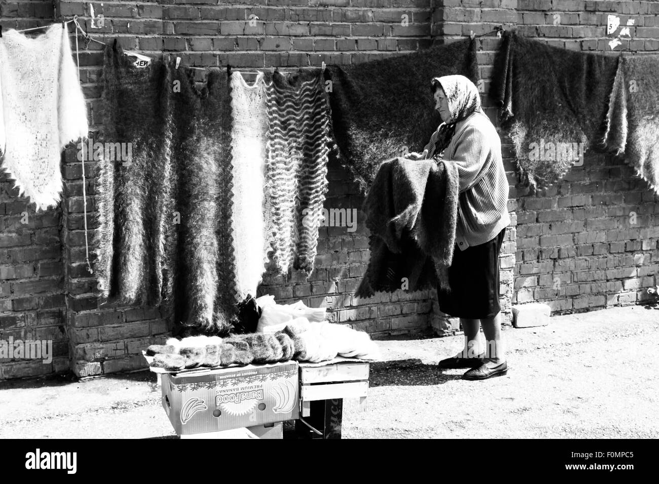 Old woman hangs hand woven lambs wool blankets for sale at a peoples market - Stock Image