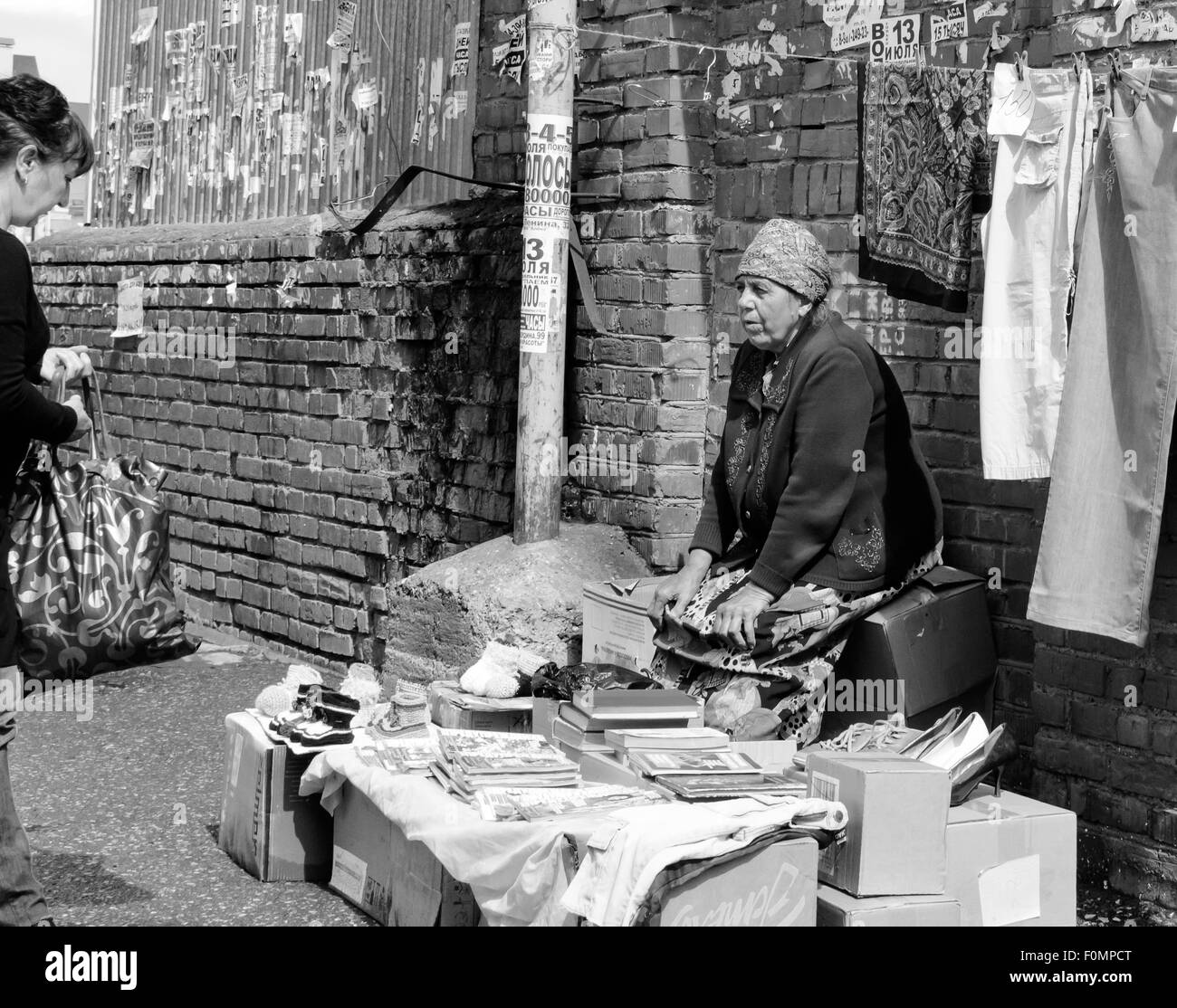 Selling old books at a market stall, an elderly pensioner or babushka converses with a potential consumer - Stock Image