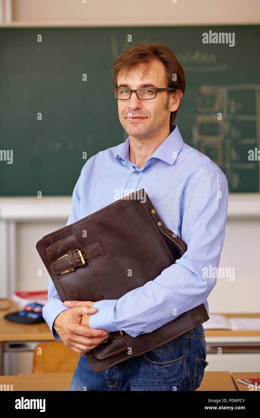 Teacher with briefcase in the classroom, portrait - Stock Image