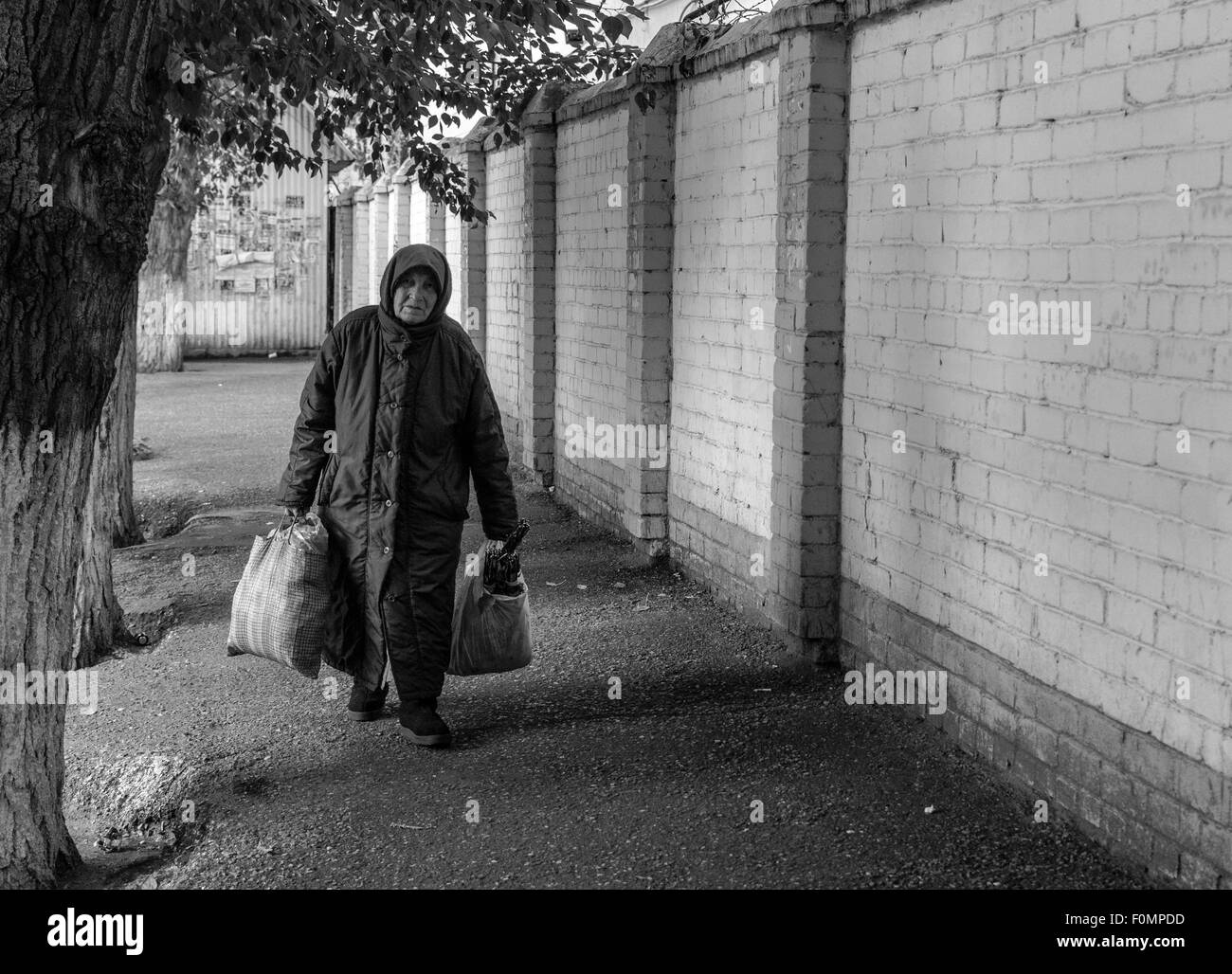 Old woman walks on a deserted path with heavy bags of shopping - Stock Image
