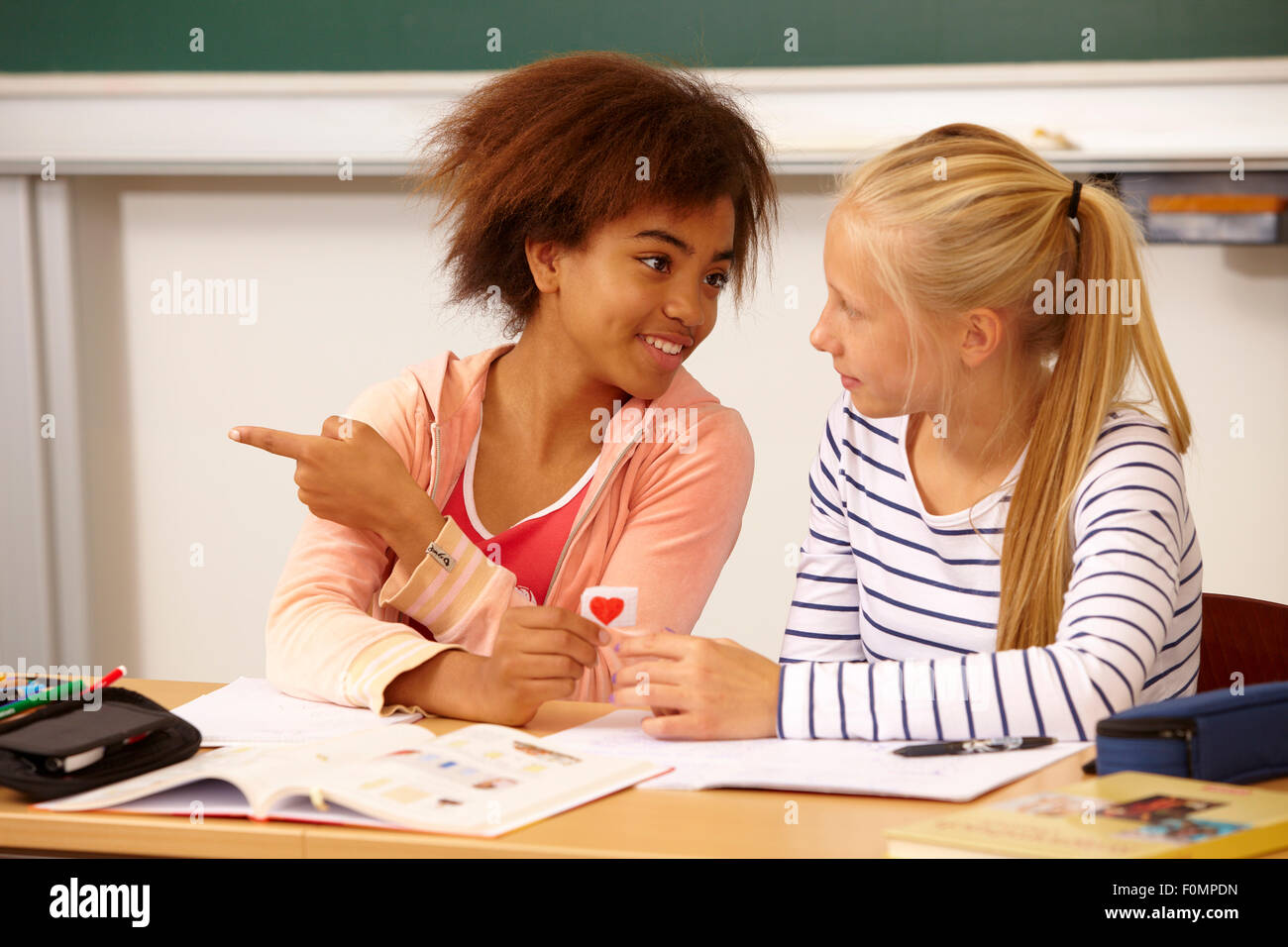 Girl hands over a love letter to her class-mate - Stock Image