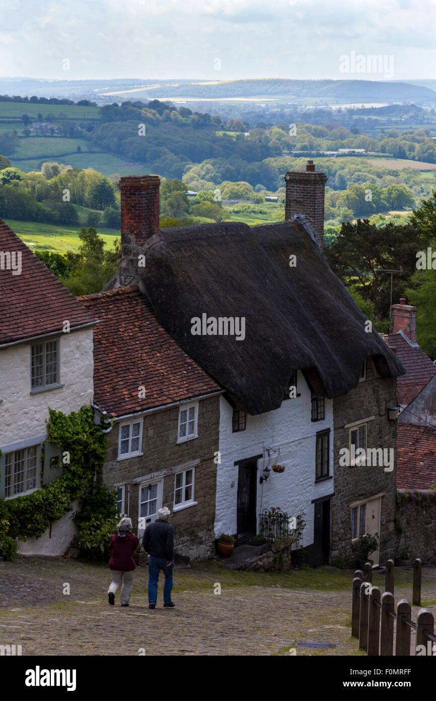 Couple strolling down Gold Hill in Shaftesbury with English green countryside in the background. - Stock Image