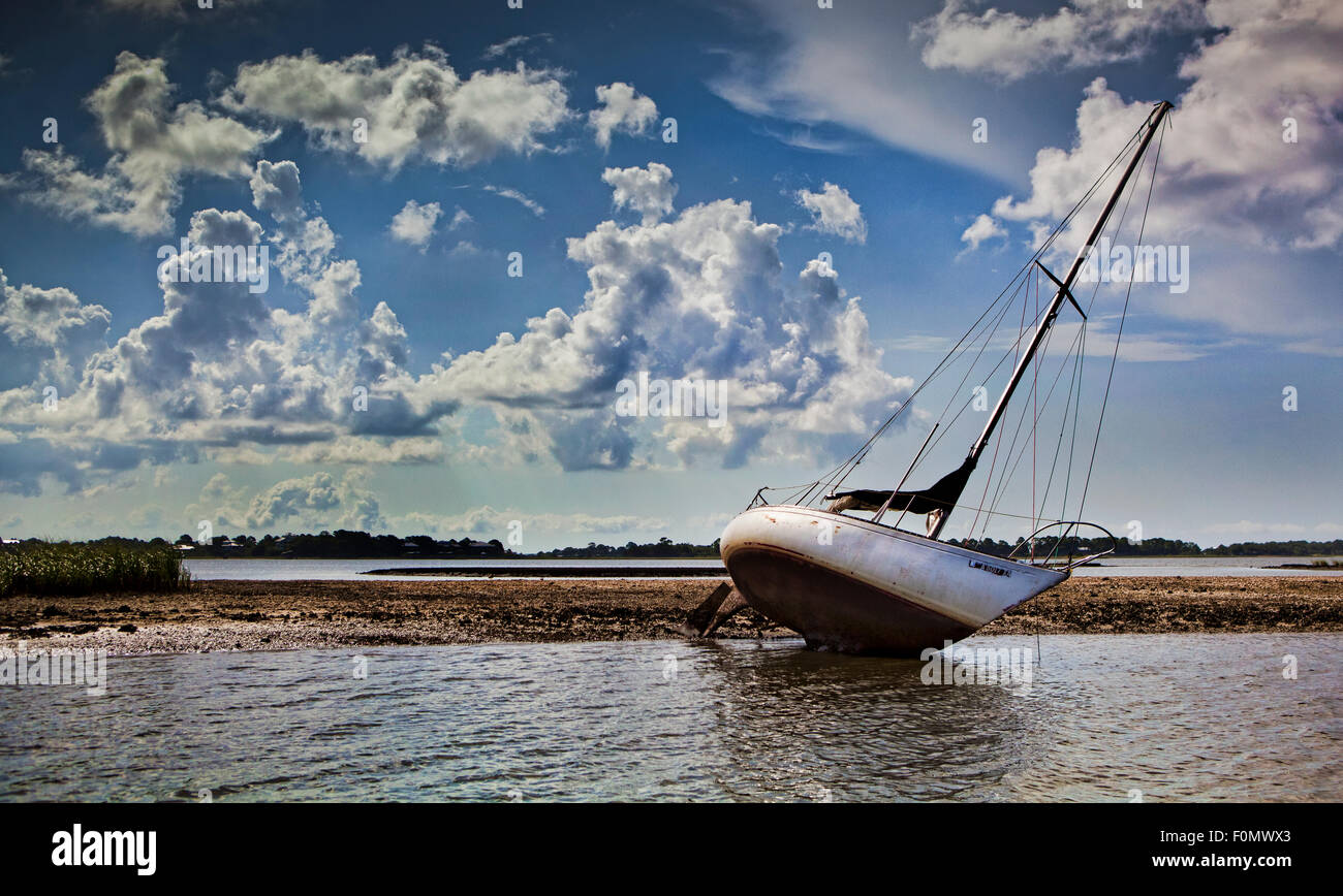 Sailboat that has run aground and is leaning over on its side due to sitting on a sandbar - Stock Image