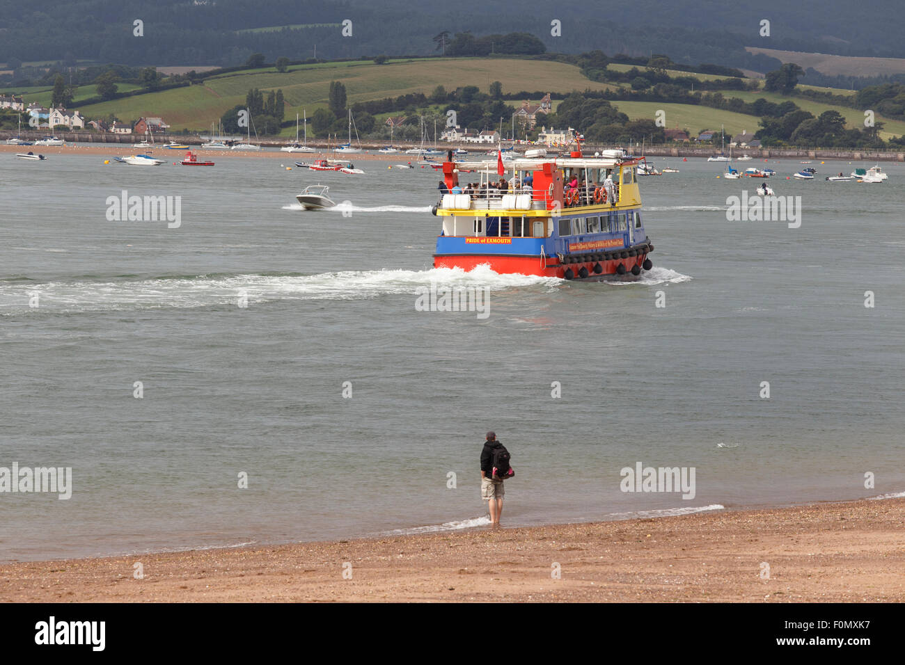 'Pride of Exmouth' ferry, watched from beach by man, cruising into mouth of the river Exe. Stock Photo