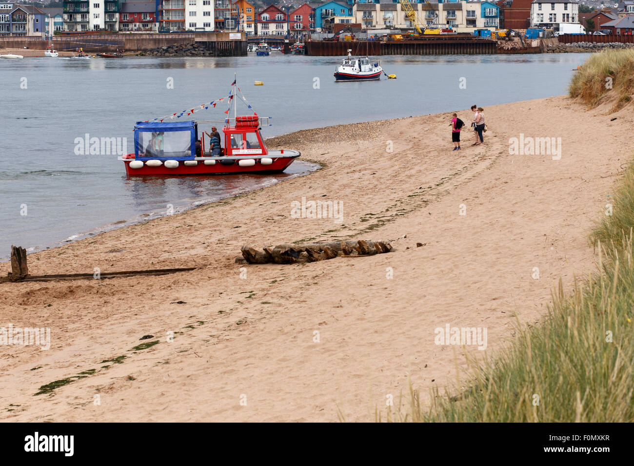 Passengers alighting from 'water taxi' at Dawlish Warren. Boat picking up passengers for return trip to - Stock Image