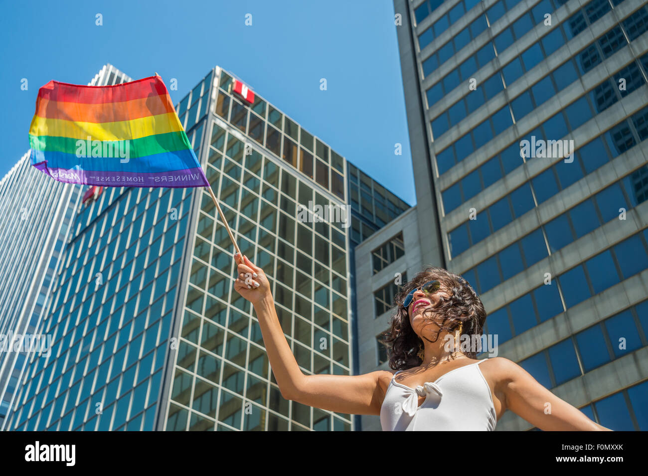 MONTREAL, CANADA, 16th August 2015. A female spectator is waving the gay rainbow flag at the 2015 Gay Pride Parade - Stock Image