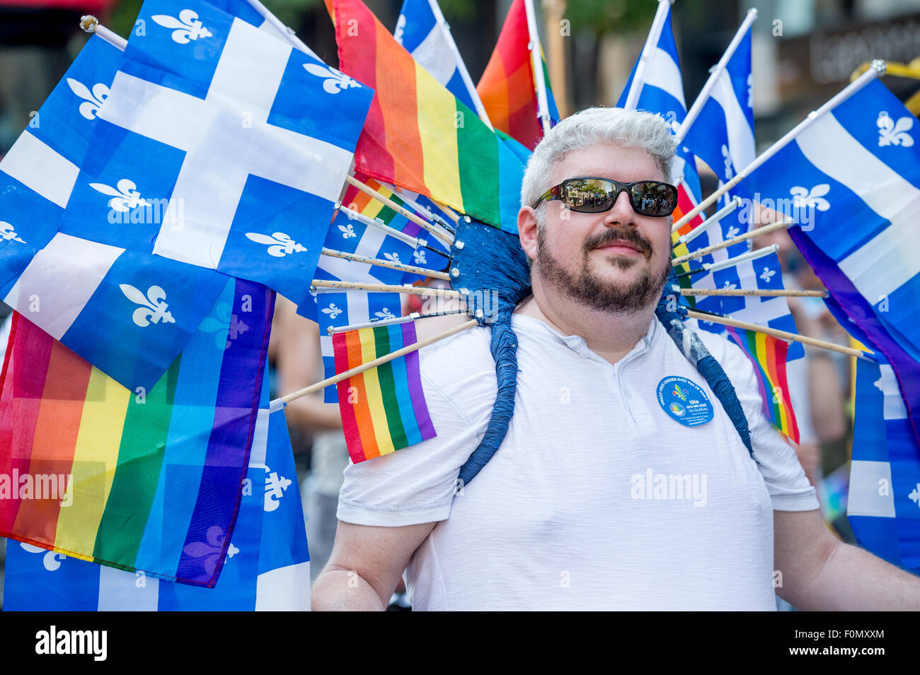 MONTREAL, CANADA, 16th August 2015. A gay participant is carrying many quebec and gay rainbow flags at the 2015 - Stock Image