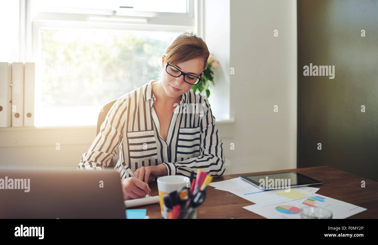 Pretty Young Businesswoman Writing Some Notes on her Desk Inside the Office Against the Glass Window. - Stock Image