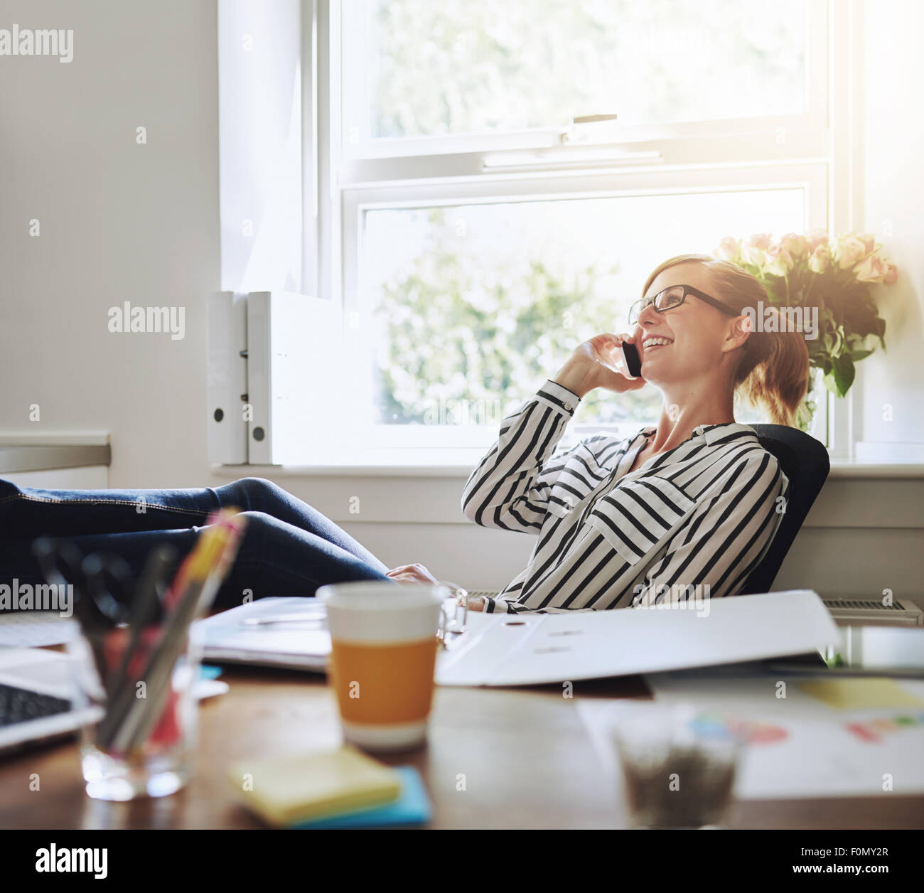 Happy Young Businesswoman Talking to Someone on her Mobile Phone While Relaxing Inside the Office with Legs on her - Stock Image