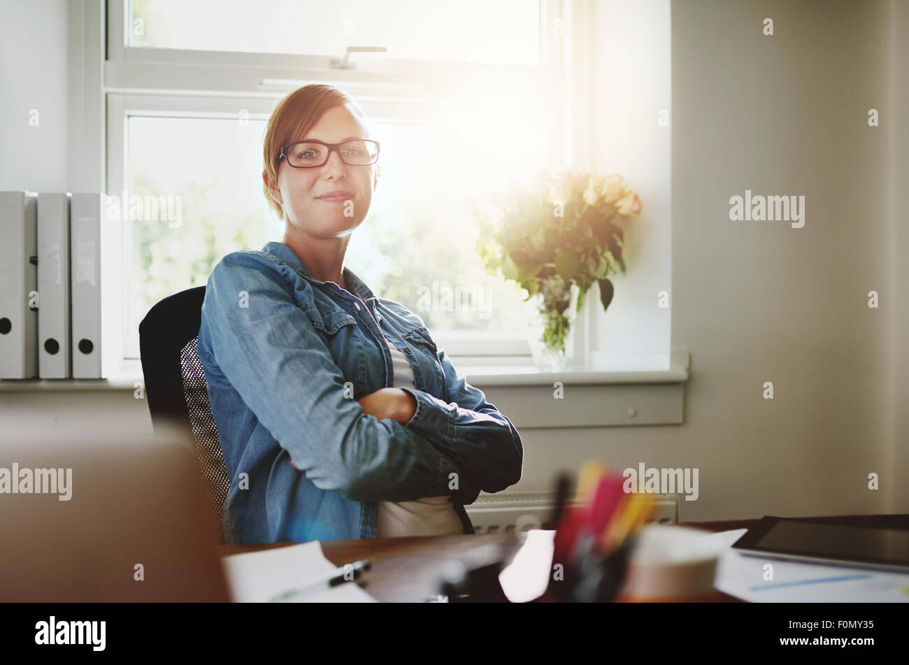 Confident Young Office Woman Sitting at her Desk with Arms Crossing Over her Stomach, Smiling at the Camera Against - Stock Image