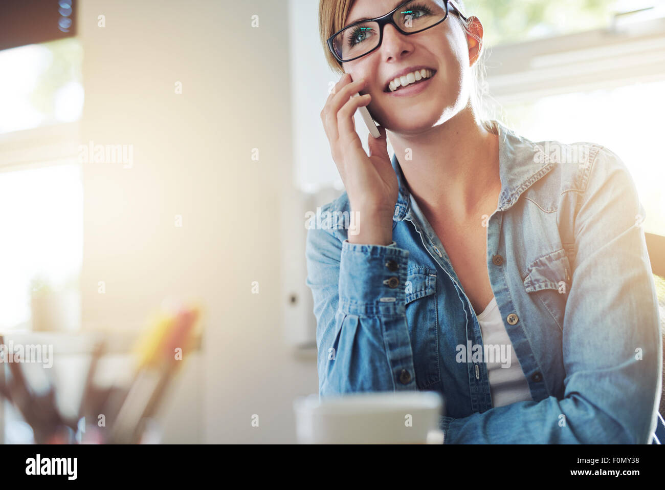 Close up Young Office Woman Talking to Someone on her Mobile Phone While Looking Into the Distance with Happy Facial - Stock Image
