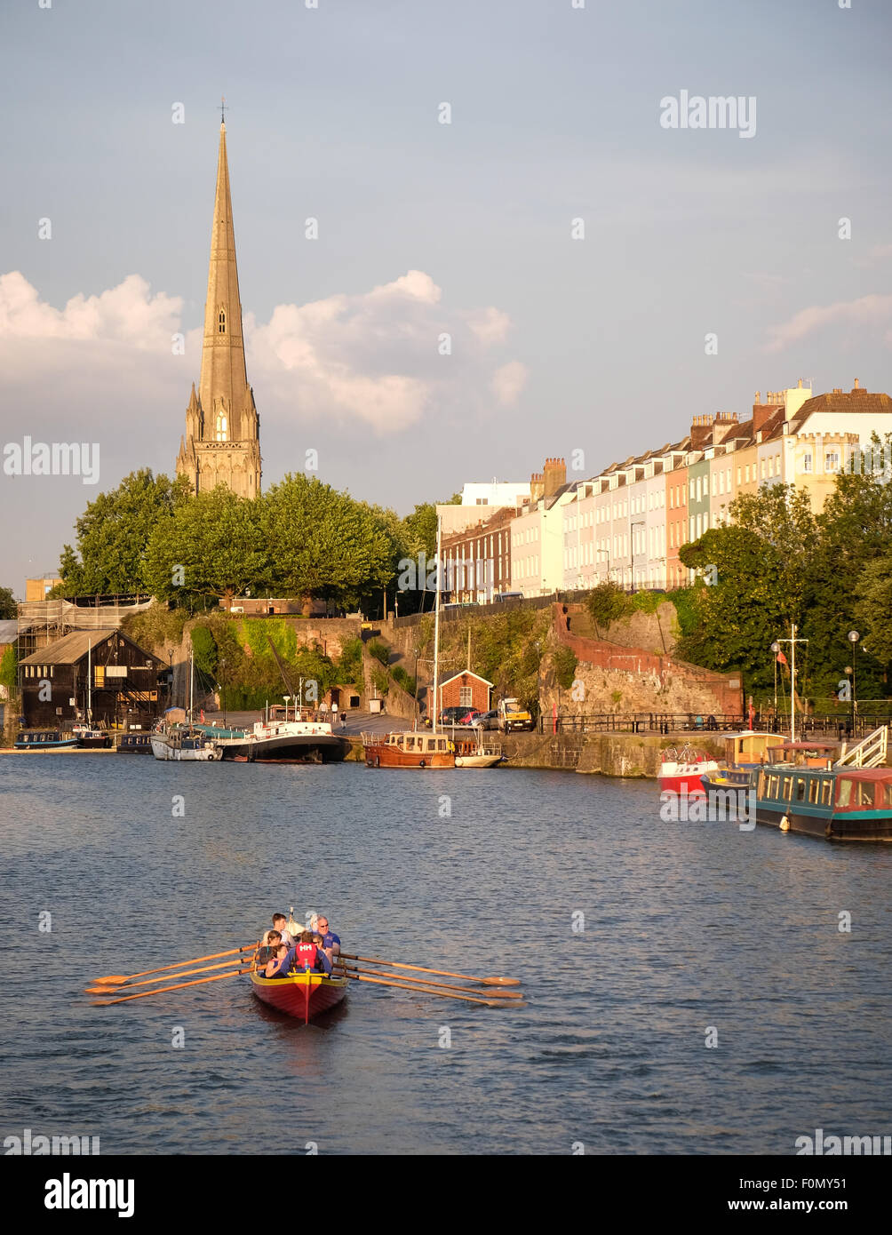 A view towards Redcliffe as gig rowers row on the floating harbour in Bristol in evening sunlight - Stock Image