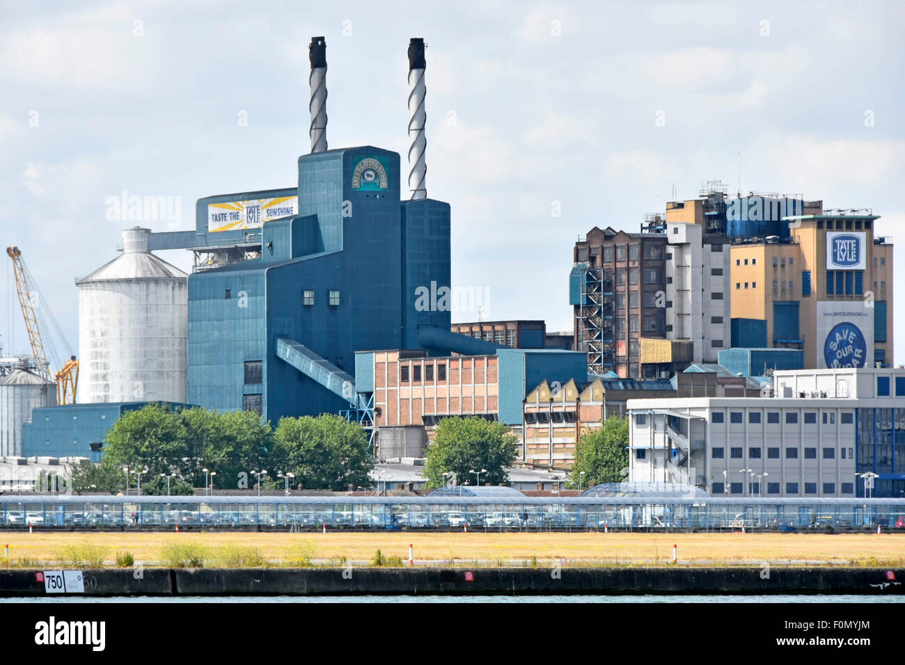 Tate and Lyle sugar refinery factory buildings seen beyond London City Airport runway London City Airport Silvertown - Stock Image