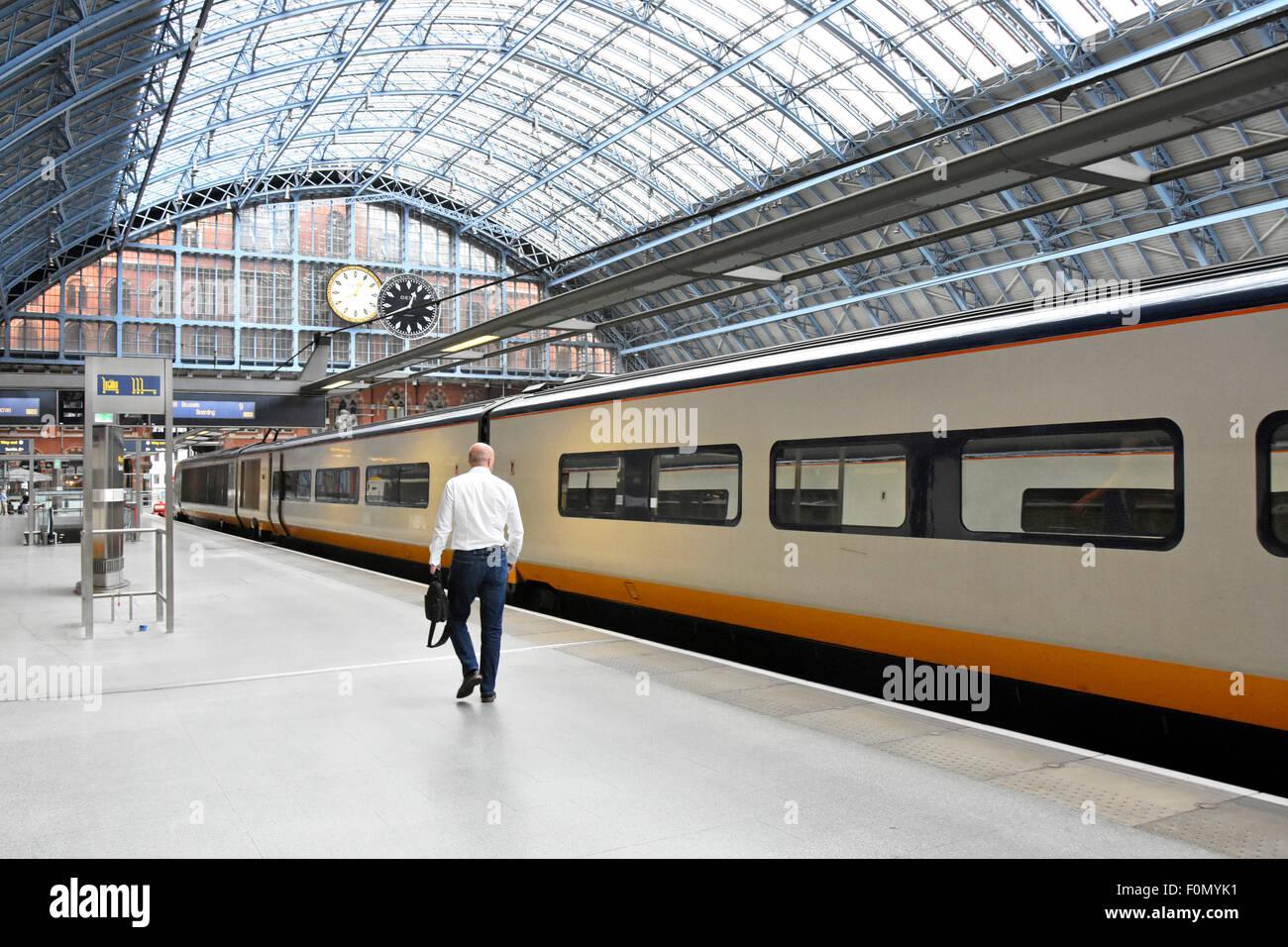 Departing lone traveller makes his way along St Pancras International Station platform to his reserved Eurostar - Stock Image