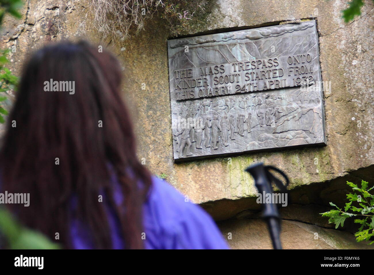 A female walker inspects the plaque in Bowden Bridge quarry that commemorates the mass trespass of Kinder Scout, - Stock Image