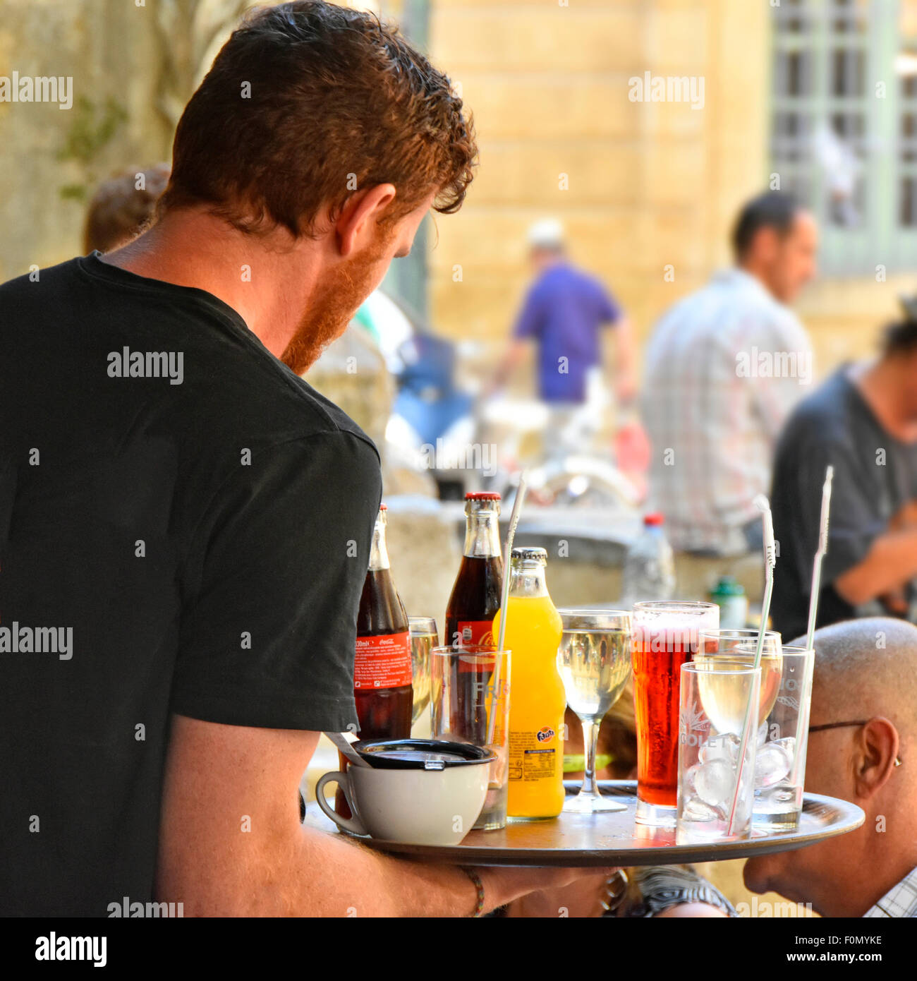 French waiter carries tray full of drinks to customers  at outdoor bar tables in Place de l'Hotel de Ville Aix - Stock Image