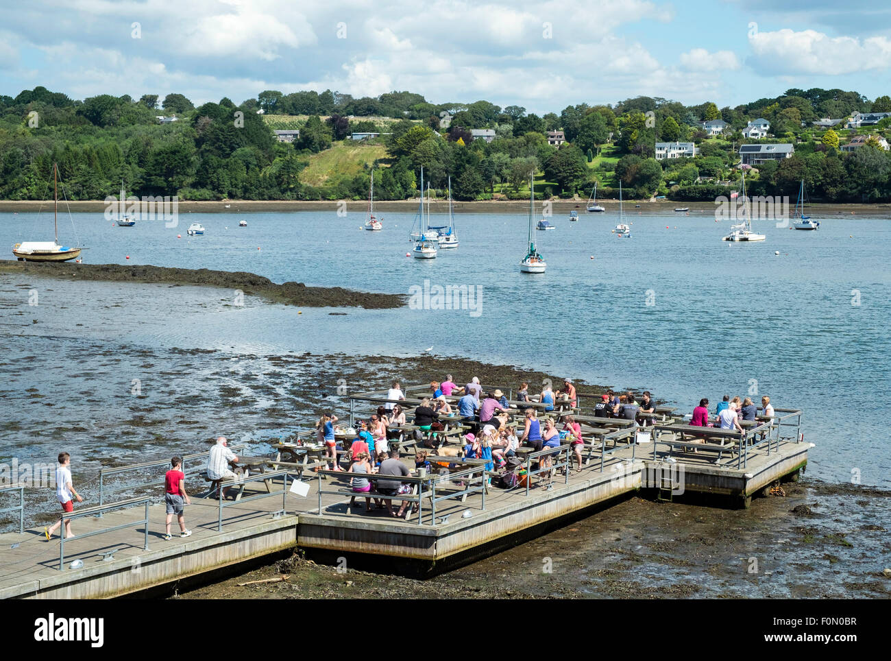 People dining on the pontoon belonging to the Pandora inn at Restronguet creek near falmouth in Cornwall, Uk - Stock Image
