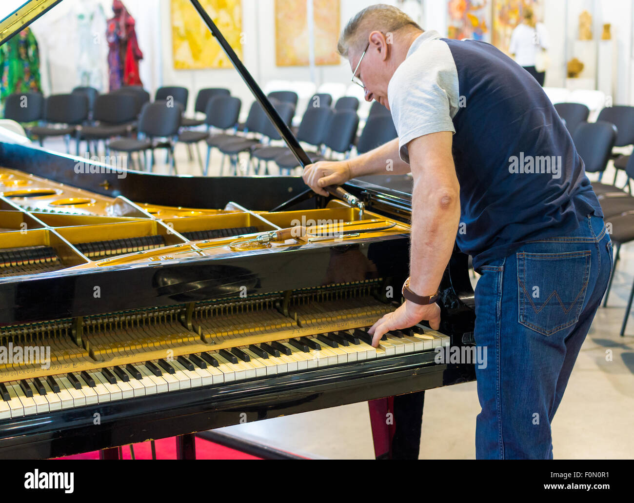 Professional piano tuner works on a grand piano before a musical performance - Stock Image