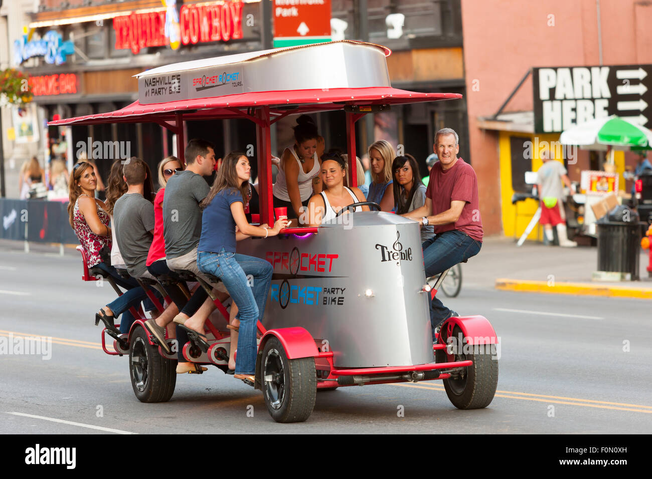 People pedal a Sprocket Rocket Party Bike on lower Broadway in Nashville, Tennessee. - Stock Image
