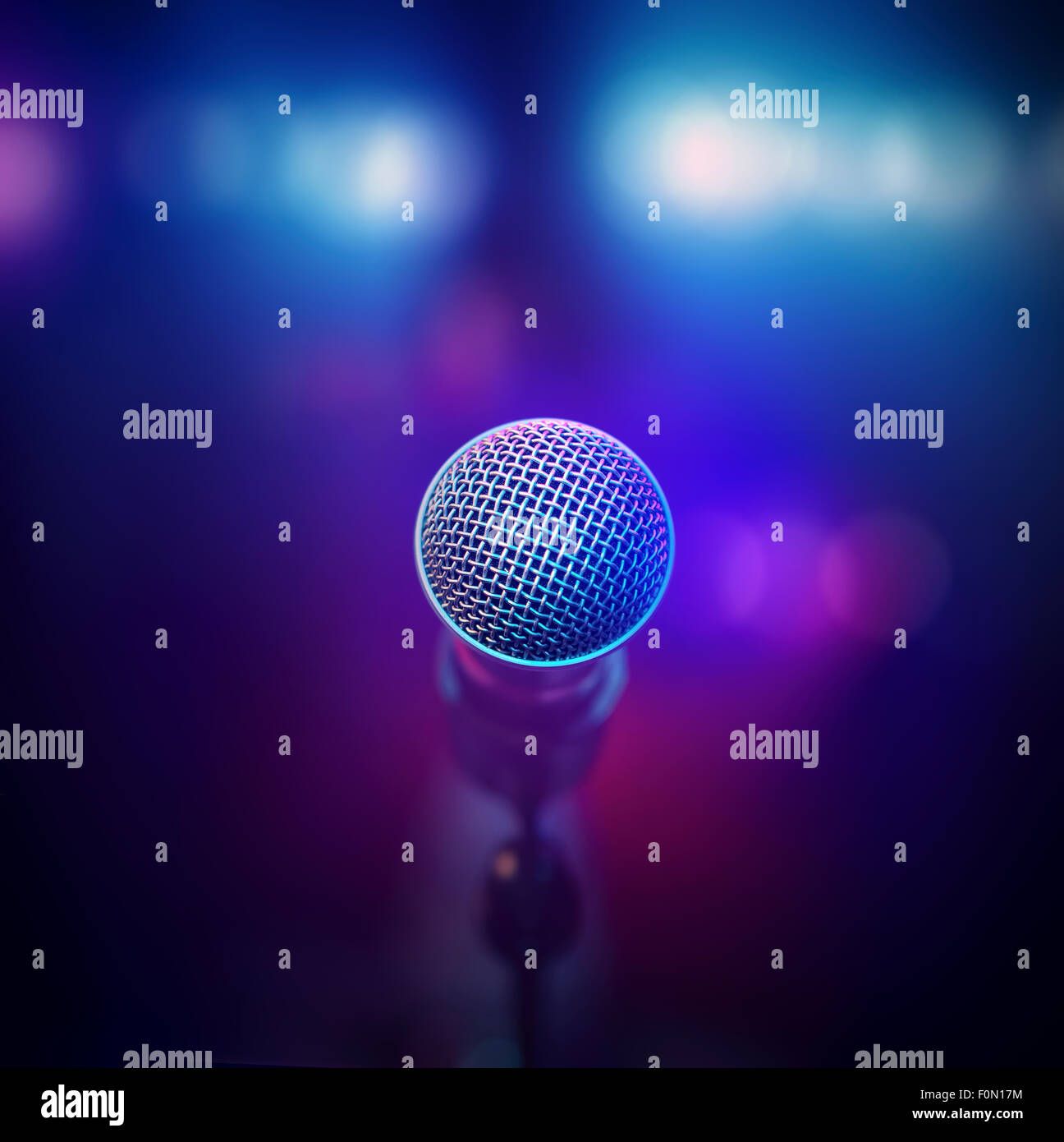 Musical microphone close-up from behind facing out of focus stage lights - Stock Image