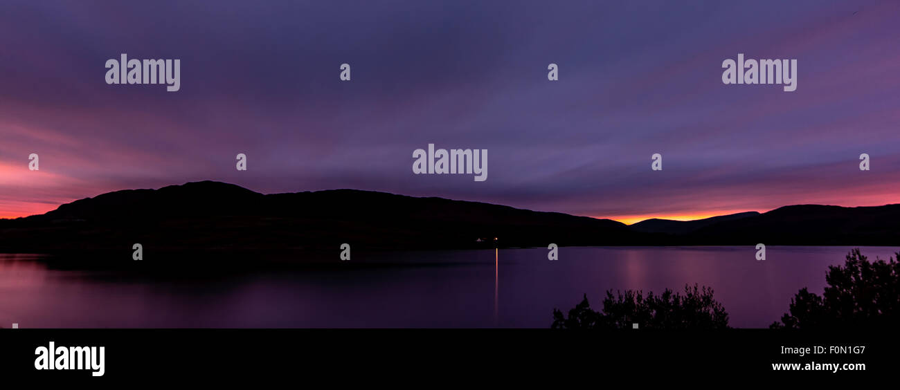 Clatteringshaws Loch in New Galloway Forest Park just after sunset on a cloudy evening. - Stock Image