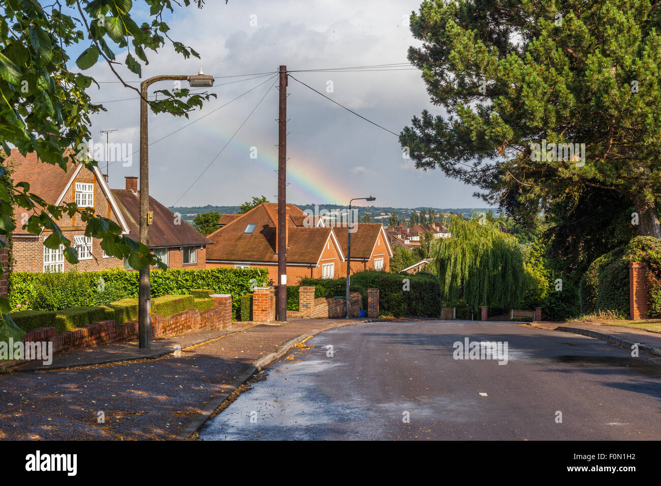 Scene of a residential area after the rain, with rainbow on the far distance, Loughton, Essex. England, UK - Stock Image