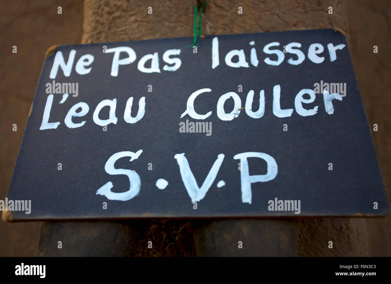 Sign board to prevent against wasting water in the Dogon Country in Mali. Message in French. - Stock Image